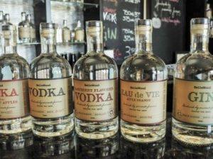 Glass bottles of Bellewood Distilling vodka and gin lined up on a bar.