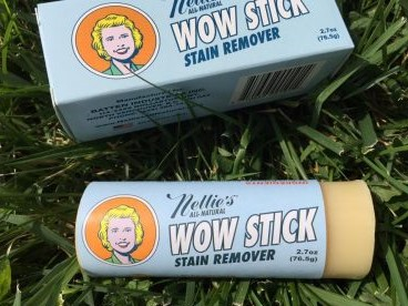 Nellie's Wow Stick lays in the grass next to its packaging.