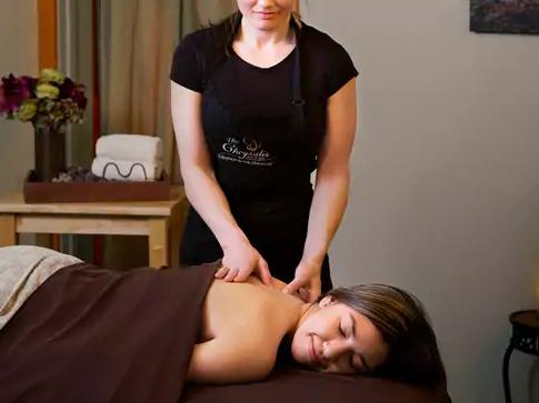 A massage therapist massages a client on a massage table.