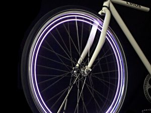 A glowing bicycle wheel light on a bicycle in the dark.