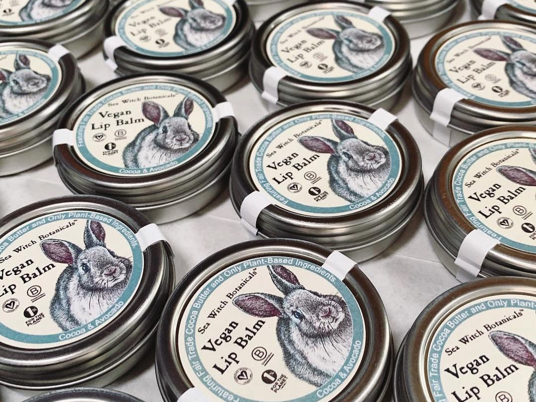 A pile of vegan lip balms and tints from Sea Witch Botanicals, with rabbits on the tins.