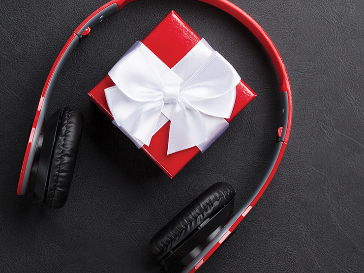 A wrapped present sits between a pair of headphones.